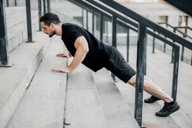 Goed gebouwde jonge man die omhoog duwt van trappen. zijaanzicht. atletische man met zwart haar in zwarte sportkleding en sneakers die op straat traint. geconcentreerde man die traint om een fit lichaam te hebben.