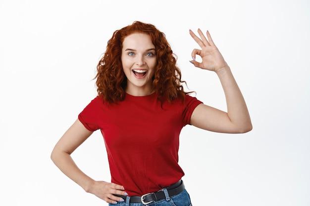 Goed gedaan. blij roodharig meisje met krullend haar zegt oke ja, oke teken tonen en tevreden glimlachen, goede zaak goedkeuren, staande over witte muur