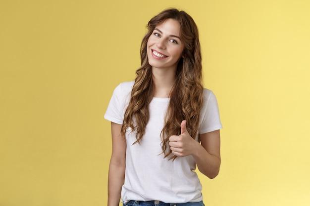 Goed gedaan gefeliciteerd. gelukkig charismatisch mooi europees vrouwelijk kantelhoofd glimlachend in grote lijnen accepteren eens uw idee zoals tevreden goed resultaat tonen duim omhoog goedkeuring gebaar gele achtergrond