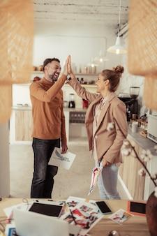 Goed gedaan. glimlachende modeontwerper die zijn schets vasthoudt en high-five geeft aan zijn vrolijke collega.