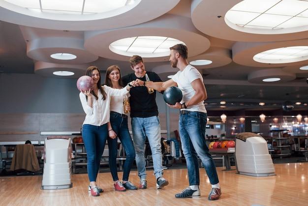 Goed gedaan. jonge, vrolijke vrienden vermaken zich in het weekend in de bowlingclub