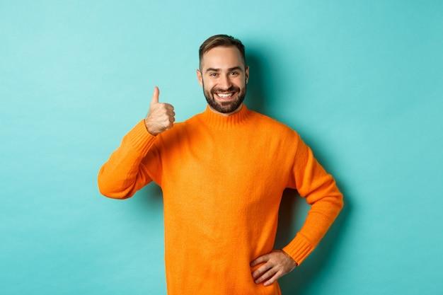 Goed gedaan. knappe bebaarde man duim opdagen, goed werk prijzend, uitstekend product aanbevelen, leuk vinden en goedkeuren, glimlachend tevreden, staande over lichtblauwe achtergrond.