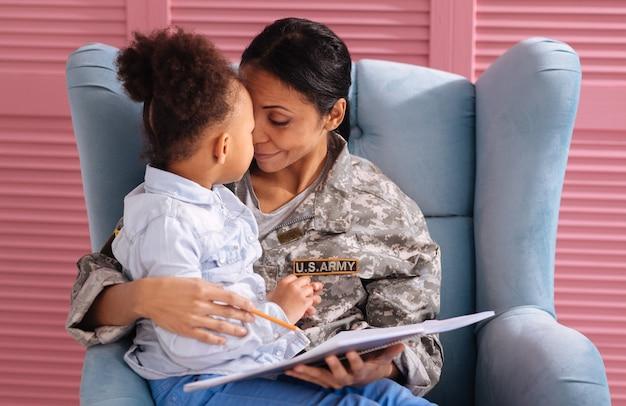 Goed gedaan, lieverd. liefdevolle aardige prachtige dame die haar kind vertelt dat ze leuke dingen schrijft terwijl ze haar knuffelt en in een stoel zit
