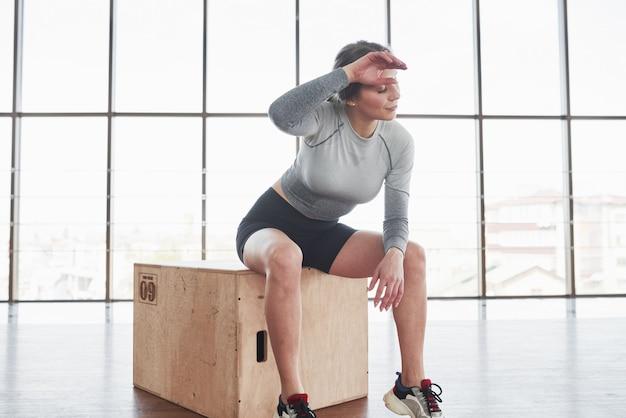 Goed gedaan. sportieve jonge vrouw heeft fitnessdag in de sportschool in de ochtendtijd