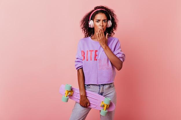 Goed geklede afrikaanse meisje poseren met longboard. portret van stijlvolle zwarte vrouw in koptelefoon staande op roze met geschokt gezichtsuitdrukking.