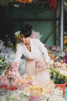Goed geklede aziatische dame die bloemen in bloemistwinkel kiest