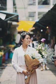 Goed geklede aziatische vrouw die door markt loopt en groot bloemboeket draagt