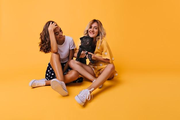 Goed geklede brunette meisje speelt met haar haar en kijken naar franse bulldog. prachtige blonde jonge dame met schattige kleine hond.