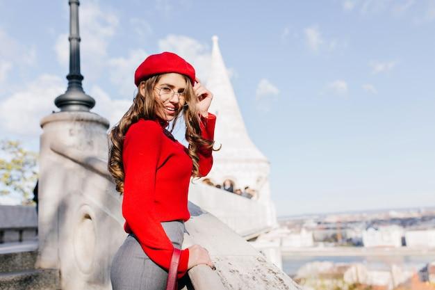 Goed geklede frans meisje in glazen genieten van uitzicht op de stad in zonnige dag