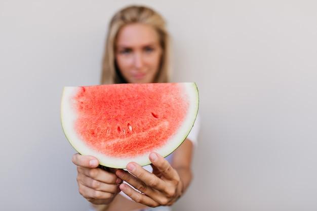 Goed geklede gelukkige vrouw met plakje watermeloen.