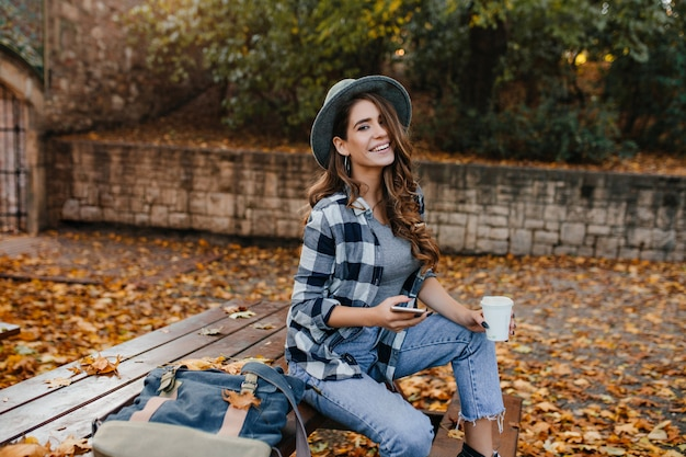 Goed geklede lachende vrouw met lichtbruin haar zittend in het park in oktober dag en genieten van uitzicht op de natuur