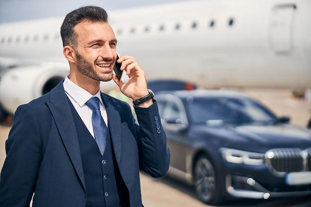 Goed geklede man aan de telefoon die bij de mooie auto staat met een vliegtuig op de achtergrond