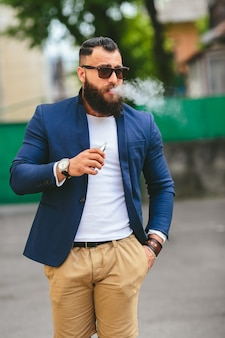 Goed geklede man die elektronische sigaret rookt