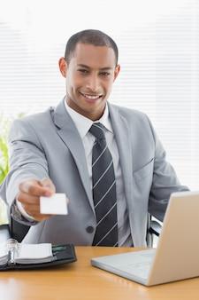 Goed geklede man die visitekaartje voor laptop op kantoor overhandigen