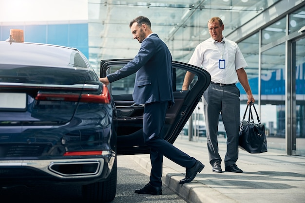 Goed geklede mannelijke reiziger stapt in een taxi terwijl een portier met zijn plunjezak bij een auto staat