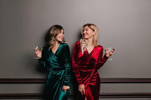 Goed geklede meisjes kijken elkaar aan terwijl ze wijn drinken. lachende vrienden die genieten van een gesprek.