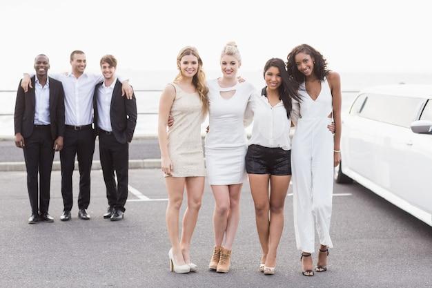 Goed geklede mensen die naast een limousine poseren