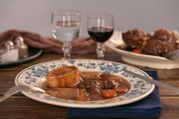 Goed gekookt rundvlees schenkel in wijnsaus geserveerd in een antieke plaat op een houten tafel