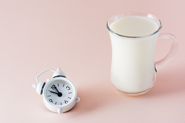 Goed geslapen. een glas melk een product om lekker in slaap te vallen en een wekker op een roze achtergrond. avondritueel