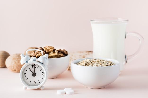 Goed geslapen. voedsel voor een goede nachtrust - melk, walnoten, havermout, slaappil en wekker op roze achtergrond