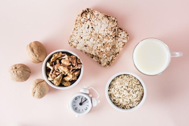 Goed geslapen. voedsel voor een goede nachtrust - melk, walnoten, knäckebröd, havermout en wekker op roze achtergrond. bovenaanzicht