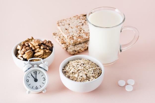 Goed geslapen. voedsel voor een goede nachtrust - melk, walnoten, knäckebröd, havermout, slaappil en wekker op roze achtergrond