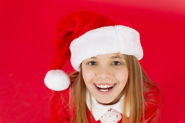 Goed gevoel. positiviteitsconcept. vrolijke stemming. kerstfeest. kerstvakantie. speelse stemming. ideeën voor kerstvieringen. kind kerstman kostuum hoed close-up. gelukkig lachend gezicht. emotionele baby.