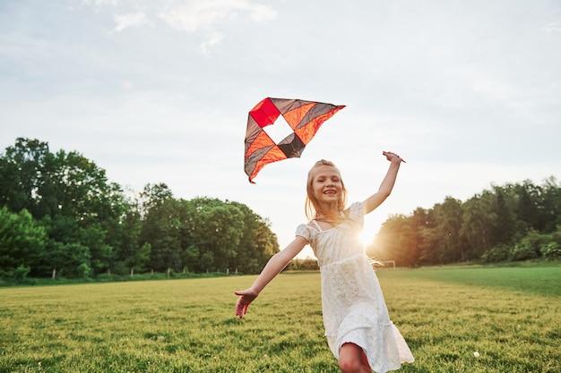 Goed gezind. gelukkig meisje in witte kleren veel plezier met vlieger in het veld. prachtige natuur.