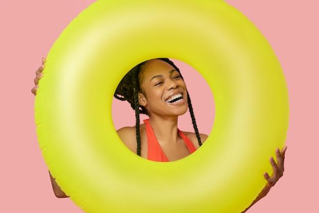 Goed gezind. glimlachende afro-amerikaanse vrouw die een gele buis vasthoudt en plezier heeft