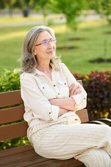 Goed gezind. glimlachende mooie volwassen vrouw met een bril in lichte kleding met gevouwen armen op de borst zittend op een bankje op zomerdag
