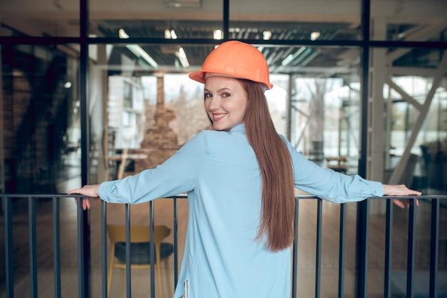 Goed gezind. glimlachende zelfverzekerde jonge langharige vrouw in veiligheidshelm kijkend naar camera binnenshuis in nieuw gebouw