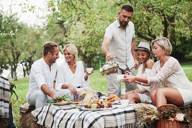 Goed gezind. groep volwassen vrienden hebben een rust en een gesprek in de achtertuin van het restaurant tijdens het diner