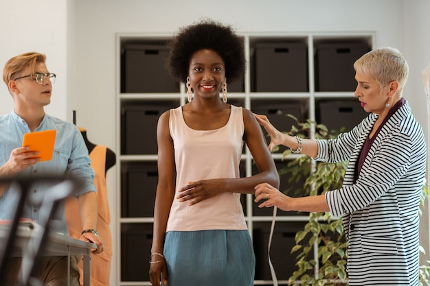 Goed gezind. jonge afro-amerikaanse vrouw staat in een studio omringd door twee modeontwerpers
