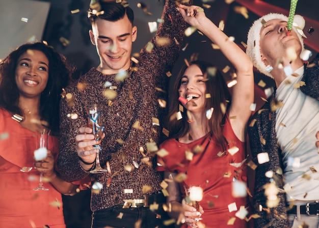 Goed gezind. lucht in de confetti. vier goede vrienden in goede kleding zijn op het feest van het nieuwe jaar