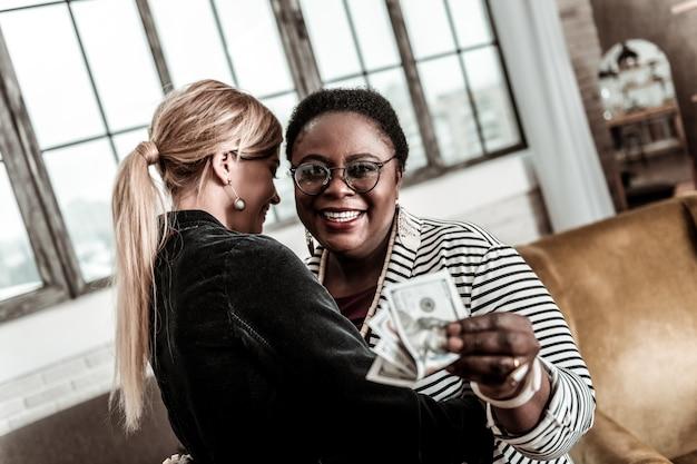 Goed gezind. mollige afro-amerikaanse vrouw die een gestreept jasje draagt en zich positief voelt