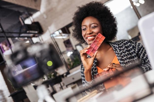 Goed gezind. mooie donkere make-up blogger in een oranje top die zich prachtig voelt terwijl ze een bericht op de blog plaatst