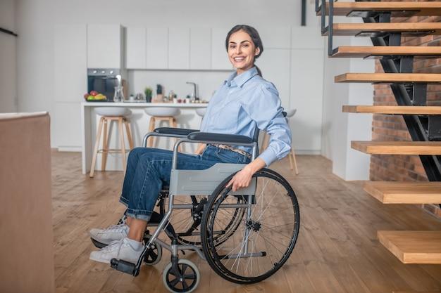 Goed gezind. positieve gehandicapte jonge vrouw thuis en er gelukkig uitzien