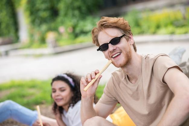 Goed gezind. roodharige gelukkige kerel in zonnebril en lichte t-shirt die grissini eet op picknick op mooie dag