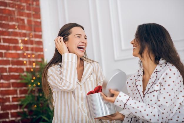 Goed gezind. twee meisjes in pyjama's openen de geschenkdoos en voelen zich geweldig