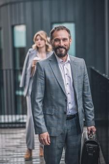 Goed gezind. vrolijke bebaarde zakenman in grijs pak met werkmap wandelen in de buurt van kantoor en jonge vrouw achter