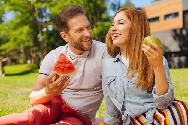 Goed humeur. alert bebaarde man watermeloen houden en praten met zijn vrouw