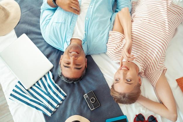 Goed humeur. gelukkig paar dat op het bed ligt met al hun spullen die samen dromen over hun zomervakantie.