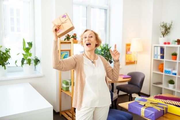 Goed humeur. gelukkige bejaarde vrouw die lacht terwijl ze haar huidige doos vasthoudt
