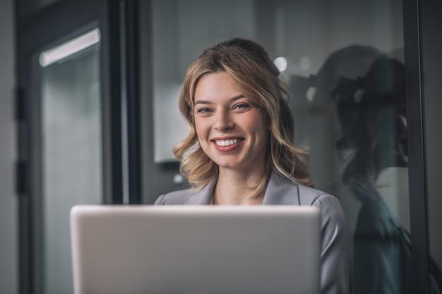 Goed humeur. gelukkige verheugende jonge bedrijfsvrouw in grijs jasje met laptop die zich in bureauruimte bevindt