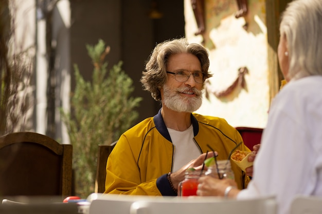Goed humeur. glimlachende man zit aan de straatcafétafel met zijn vrouw en eet taco's met fruitsmoothies.