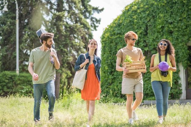 Goed humeur. vrolijke communicerende jonge mensen in comfortabele vrijetijdskleding gaan op zomerpicknick in groen park