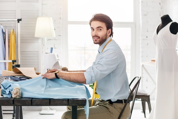 Goed humeur. vrolijke ervaren kleermaker die lacht en werkt aan een naaimachine
