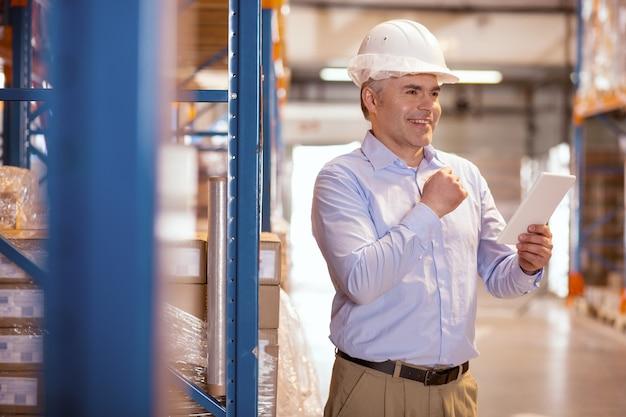 Goed humeur. vrolijke gelukkige man die lacht terwijl hij tevreden is over het werkproces in het magazijn