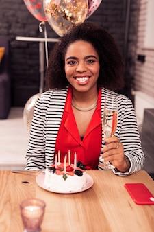 Goed humeur. vrolijke positieve vrouw met een glas champagne tijdens een verjaardagsfeestje