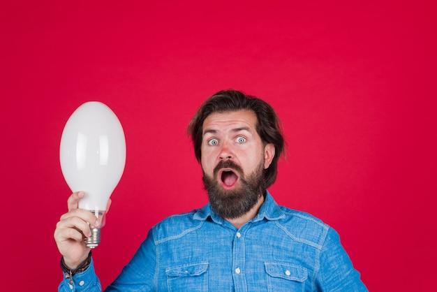 Goed idee idee lamp in de hand verraste man met grote lamp gedachten idee concept bebaarde man houdt